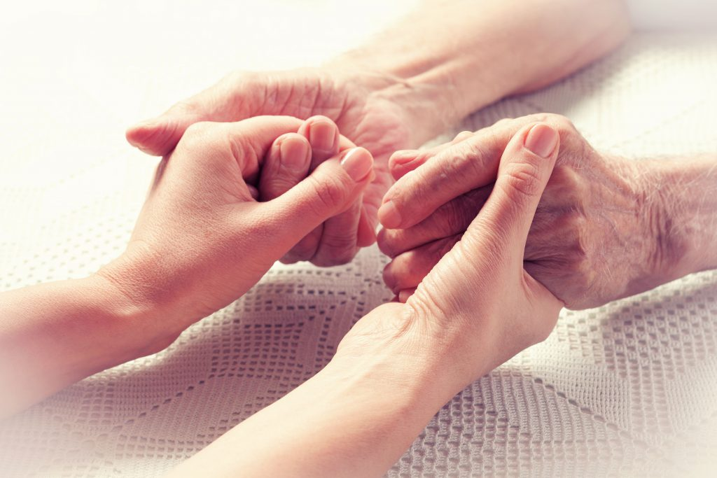 Geriatric nurse and older patient hold hands