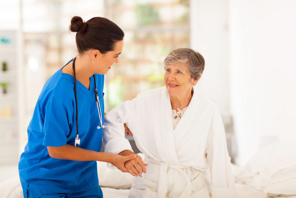 Geriatric nurse helping an older woman stand up