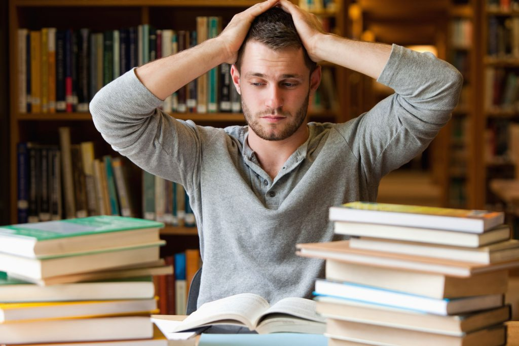male student overwhelmed with studying