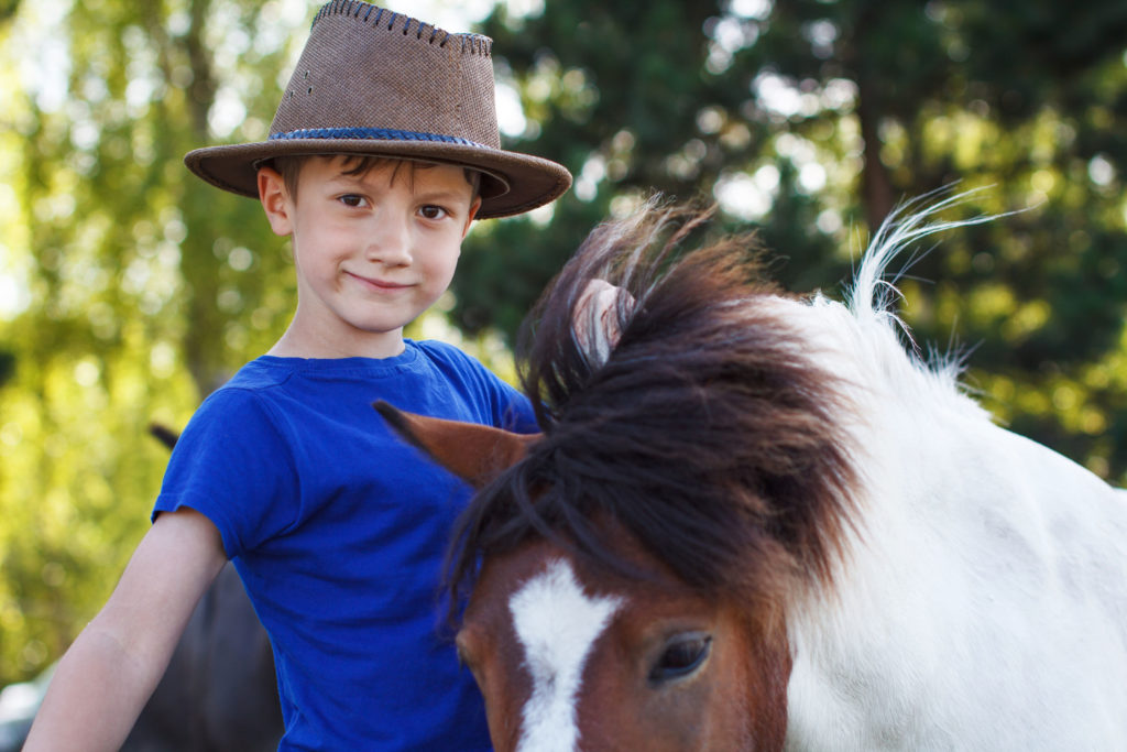 little boy with pony on farm, horse therapy
